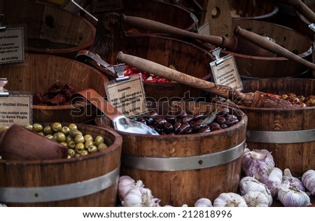 olives in a wooden barrel sold at a market - stock photo