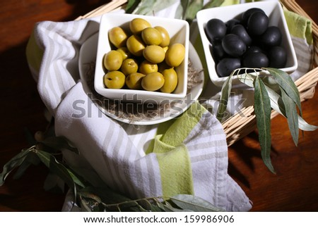 Olives in bowls with branch on napkin in basket on wooden table