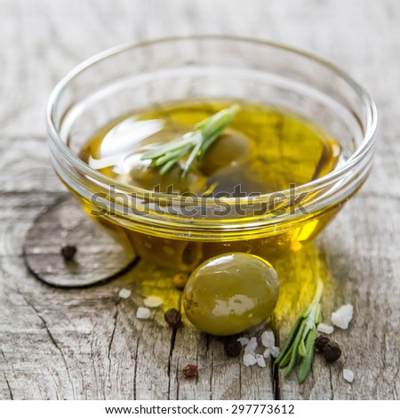 Olives in glass bowl with oil, rosemary, salt, pepper, rustic wood background - stock photo