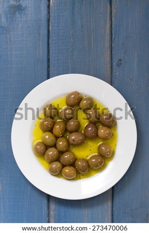 olives in olive oil on white plate on blue background