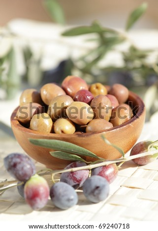 Olives in the wooden bowl and olive branches