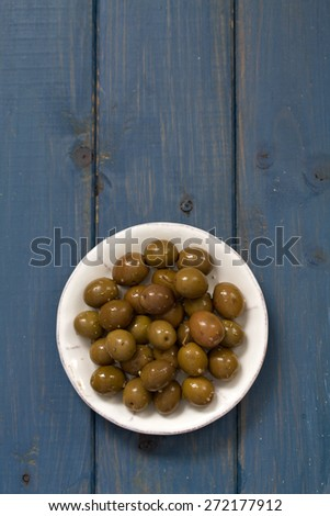olives in white dish on blue background - stock photo
