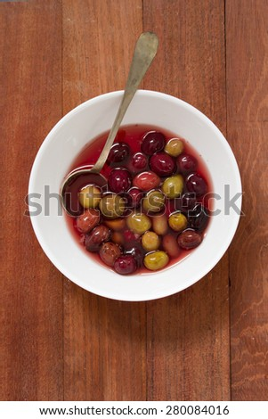 olives in white dish with spoon on brown wooden background