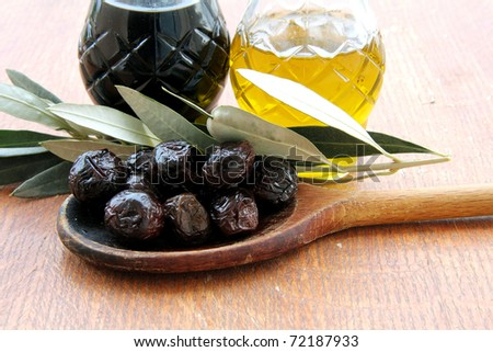 Olives , Olive Oil and balsamic vinegar on a wooden table - stock photo