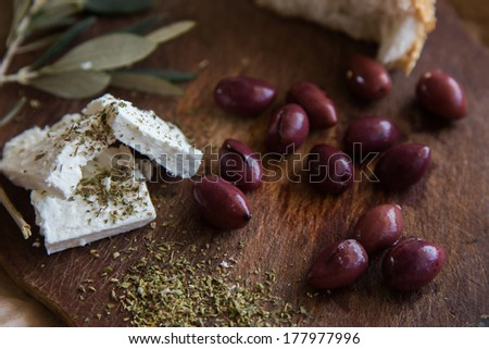 Olives on a wooden table and feta cheese - stock photo