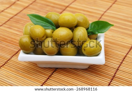 Olives on twig isolated in white plate on bamboo mat  - stock photo