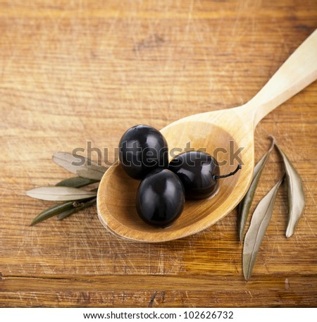 Olives over  on the spoon Wooden Background - stock photo