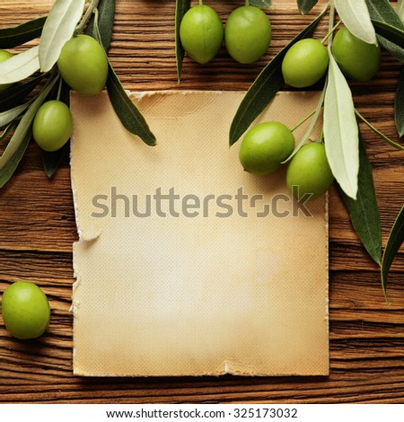 Olives over wooden background and olive oil label - stock photo