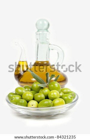 Olives with a bllurred oil bottle behind