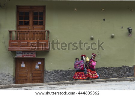 Ollantaytambo, Peru - december 18, 2014: Women and children in traditional Peruvian clothes break from posing with tourists - stock photo