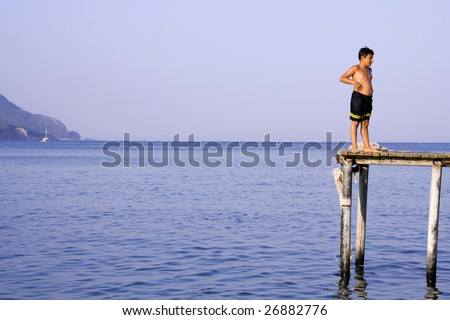 OLYMPOS, TURKEY -  AUGUST 3: A local boy ready to jump into sea from pier on August 3, 2007 in Olympos, Turkey. Olympos is located 90 km southwest of Antalya city near Kemer. - stock photo