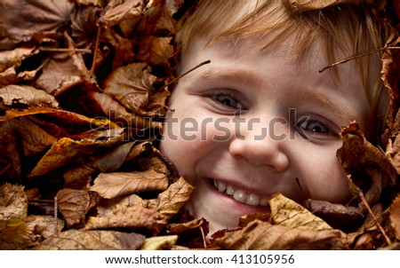 Omage of a 4 year old boy's face appearing from underneath autum leaves. The boy is happy with a smile. Leaves have turned brown. - stock photo