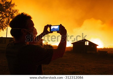 Omak, WA, USA August 19, 2015: Onlooker takes video with cell phone as flames rapidly approach buildings and property.  Okanogan Complex Fire, Washington state's largest, most destructive fire ever - stock photo