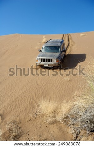 OMAN - MARCH 5, 2006: A Dubai-registered Jeep Commander 4x4 vehicle negotiates a steep dune while driving offroad in the interior of the Sultanate of Oman.