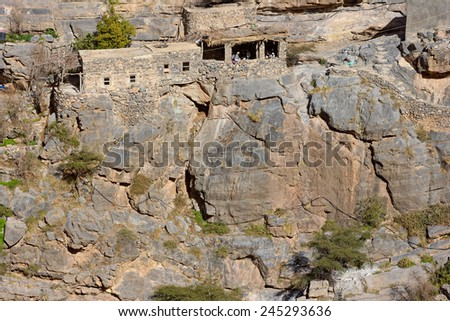 Omani men in their majlis, or meeting place, precariously set amidst traditional stone houses in a small cliff hamlet near Sroot in the Jebel Akhdar mountains of the Sultanate of Oman. - stock photo
