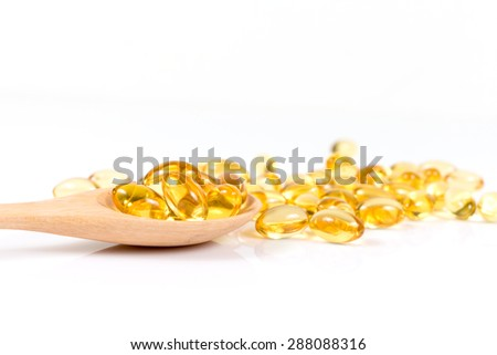 Omega 3 fish oil capsules on wooden spoon. - stock photo
