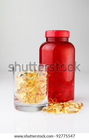 Omega 3 oik fish capsules with red plastic bottle and glass cup on white background focused to glass cup - stock photo
