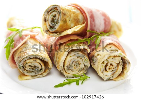 Omelet roll ups with herb wrapped in a bacon - stock photo