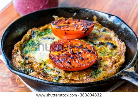 Omelet with tomato and greens on cast iron frying pan. Rustic breakfast omelette with grilled tomato and herbs. Selective focus, shallow dof - stock photo