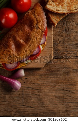 Omelet with vegetables and toast on wooden cutting board - stock photo