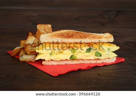 omelette sandwich with fries on red napkin - stock photo