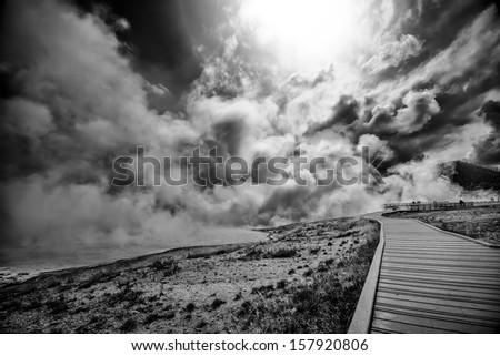Ominous clouds and steam rising over Yellowstone's Geyser Basin - stock photo