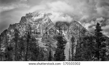Ominous clouds blanketing the Teton mountain peaks in Wyoming - stock photo