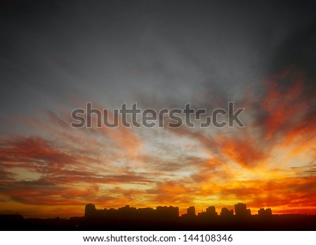 Ominous glowing sunset over a dark landscape. - stock photo