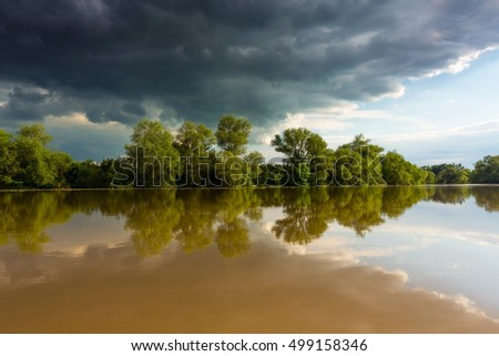Ominous stormy sky over natural flooded river, with bright sun emerging from under the cumulus cloud cover