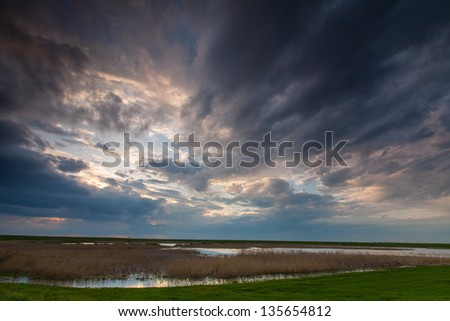 Ominous stormy sky over natural lake - stock photo