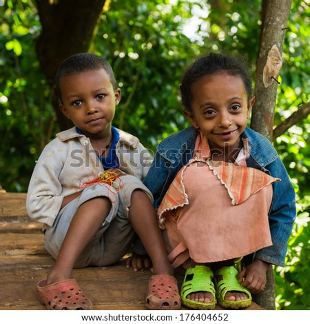 OMO, ETHIOPIA - SEPTEMBER 20, 2011: Unidentified Ethiopian beautiful little girl sits in green sleepers with her brother. People in Ethiopia suffer of poverty due to the unstable situation - stock photo