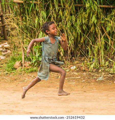 OMO, ETHIOPIA - SEPTEMBER 19, 2011: Unidentified Ethiopian girl runs happily. People in Ethiopia suffer of poverty due to the unstable situation - stock photo
