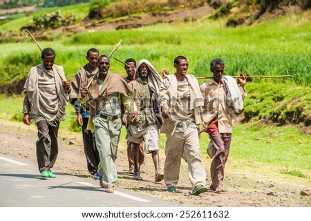 OMO, ETHIOPIA - SEPTEMBER 21, 2011: Unidentified Ethiopian men walk on the road. People in Ethiopia suffer of poverty due to the unstable situation