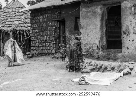 OMO, ETHIOPIA - SEPTEMBER 21, 2011: Unidentified Ethiopian woman cooks near a house. People in Ethiopia suffer of poverty due to the unstable situation