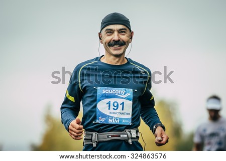 Omsk, Russia -  September 20, 2015: attractive athlete runner middle-aged distance running and smiling during Siberian international marathon - stock photo