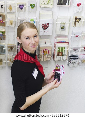 Omsk, Russia  - September 19, 2009: smiling girl seller - consultant with valentines cards  in hands at stand with cards - stock photo