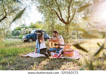 On a beautiful sunny day, a couple of young lovers, makes picnic on grass among olive groves in Tuscany, Italy. Man leans on guitar while talking with his girlfriend. Behind them a blue vintage car - stock photo