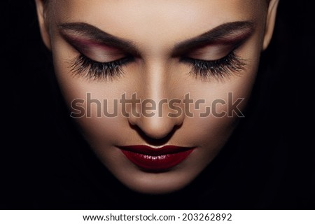 on a black background beautiful woman's face - stock photo