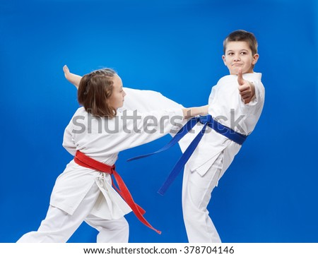 On a blue background athletes train blocks and kicks of karate - stock photo