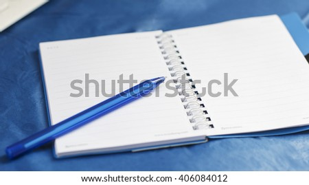 on a blue background - the notebook and blue pen for the writing, recording, performing tasks - stock photo