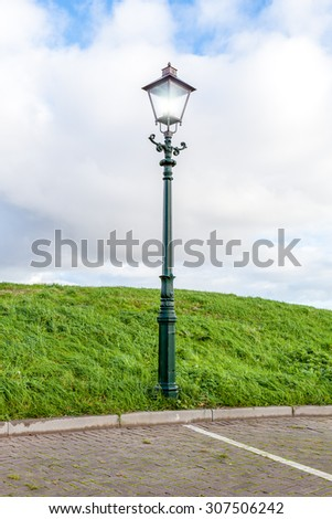 on a cloudy day is to burn this street lamp in the evening - stock photo