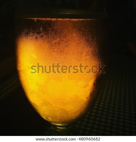 on a dark background and illuminated glass glass of beer