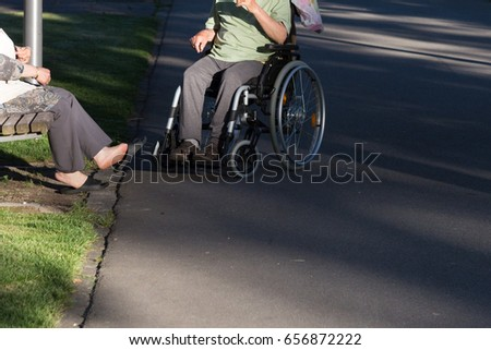 on a evening in june in south germany in center park of a historical city you see couple with wheelchair moving through shadow giving park
