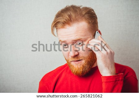 on a gray background, bearded man in a red shirt talking on the phone