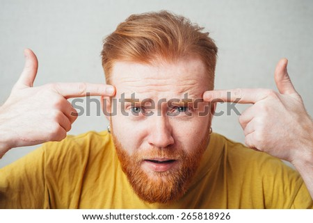 on a gray background man with a beard in the yellow shirt is outraged and shows index fingers on his head