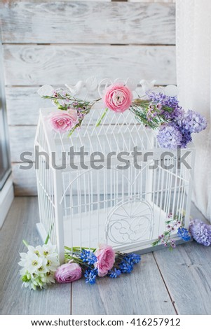 on a gray background white wooden bird cage decorated with flowers - stock photo