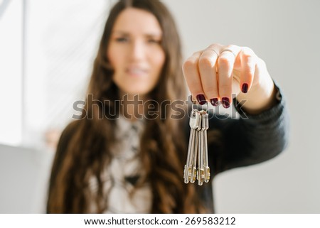 on a gray background young girl holds the keys - stock photo