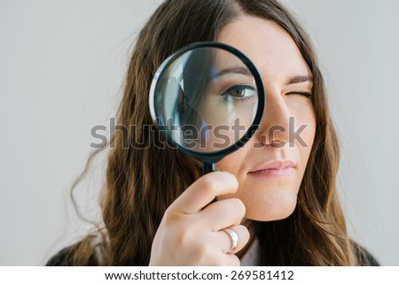 on a gray background young girl looking through a magnifying glass - stock photo