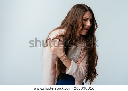 on a gray background young girl sore shoulder - stock photo