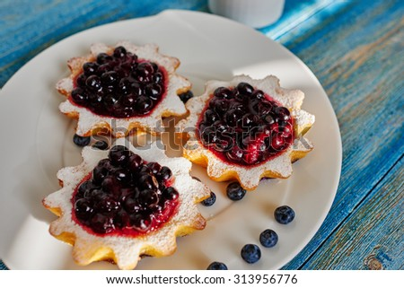 On a large white plate cook laid out freshly cooked basket of unleavened dough with Fresh jam of blueberries, currants and blueberries - stock photo
